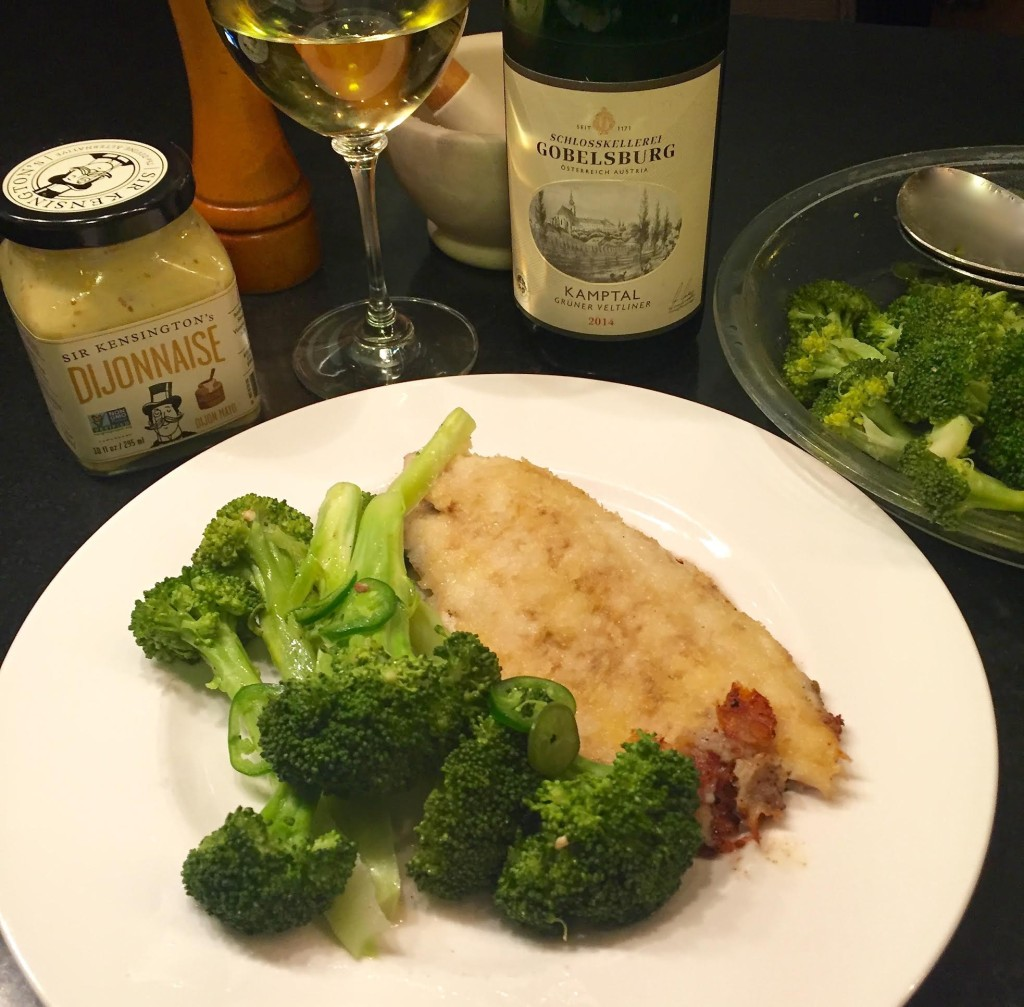 Dijonnaise catfish with steamed broccoli on a white plate.