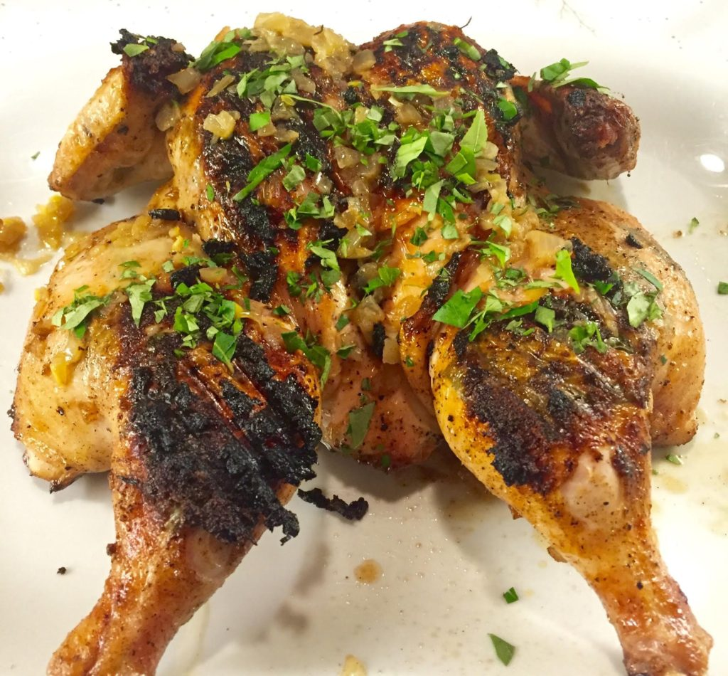 Grilled whole chicken with fresh curry leaves on a white platter.