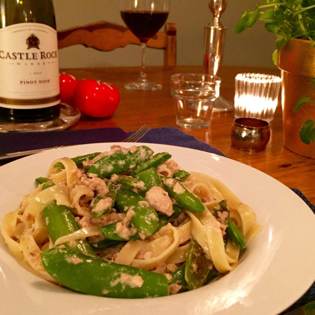 Fettuccine with salmon and sugar snap peas in a white rimmed bowl.