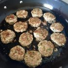 Lemon-scented pork sausage patties frying in pan.