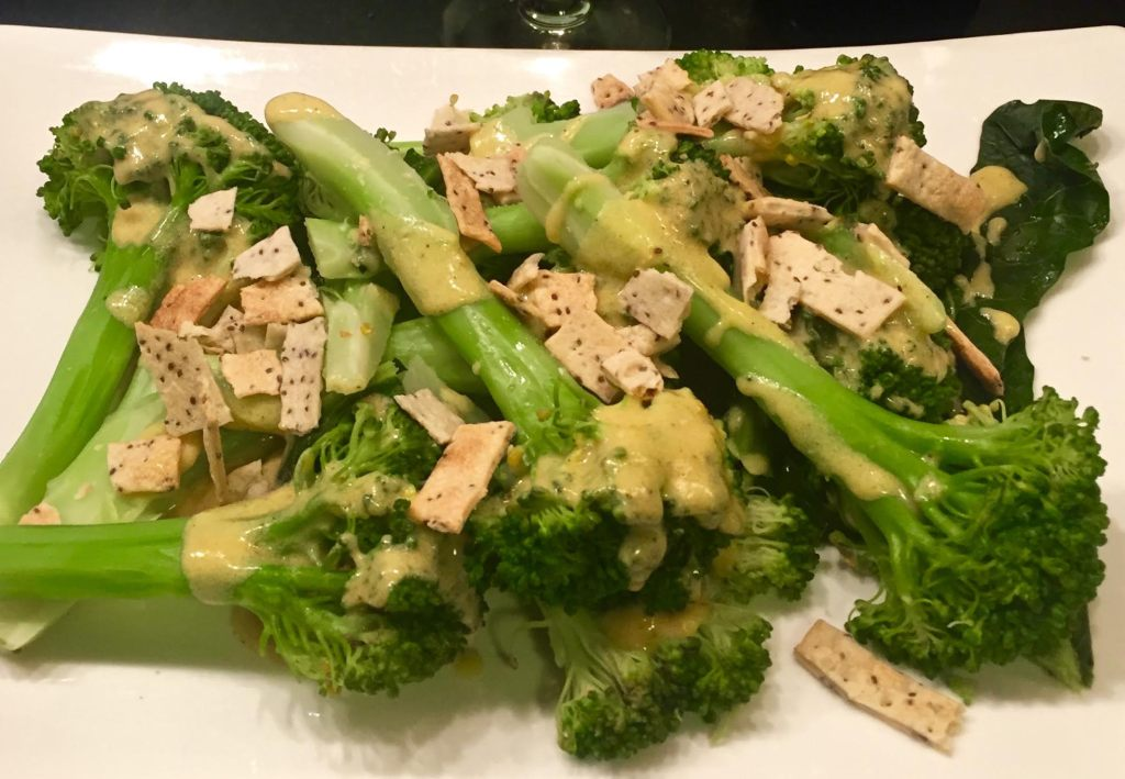 Carrie Mae's Kitchen Chia Seeds Crunchy Strips topping a finished broccoli dish on a white platter.
