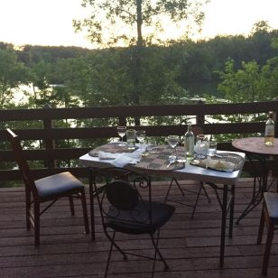 Dinner table on a deck overlooking a lake.
