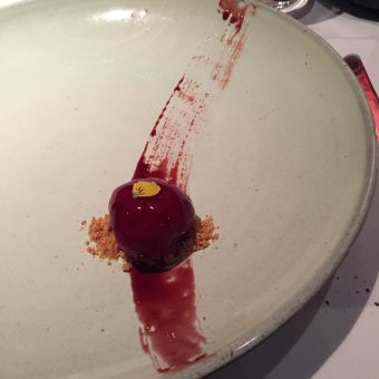 Nolita foie gras bon bon with reduced port, beet and blood orange juice on a bed of crumbled brioche.