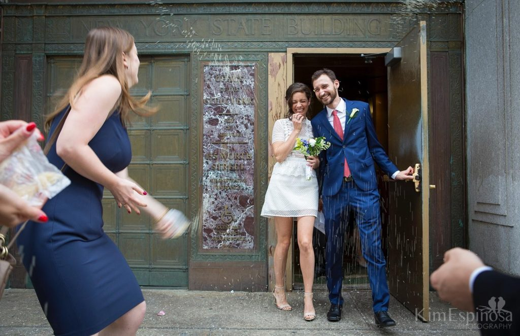 Wedding couple leaving NYC City Hall with rice being thrown.