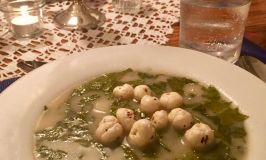 Mom's Popped Lotus Seeds garnishing a tangy sorrel & potato with bacon soup in a white flat soup bowl.