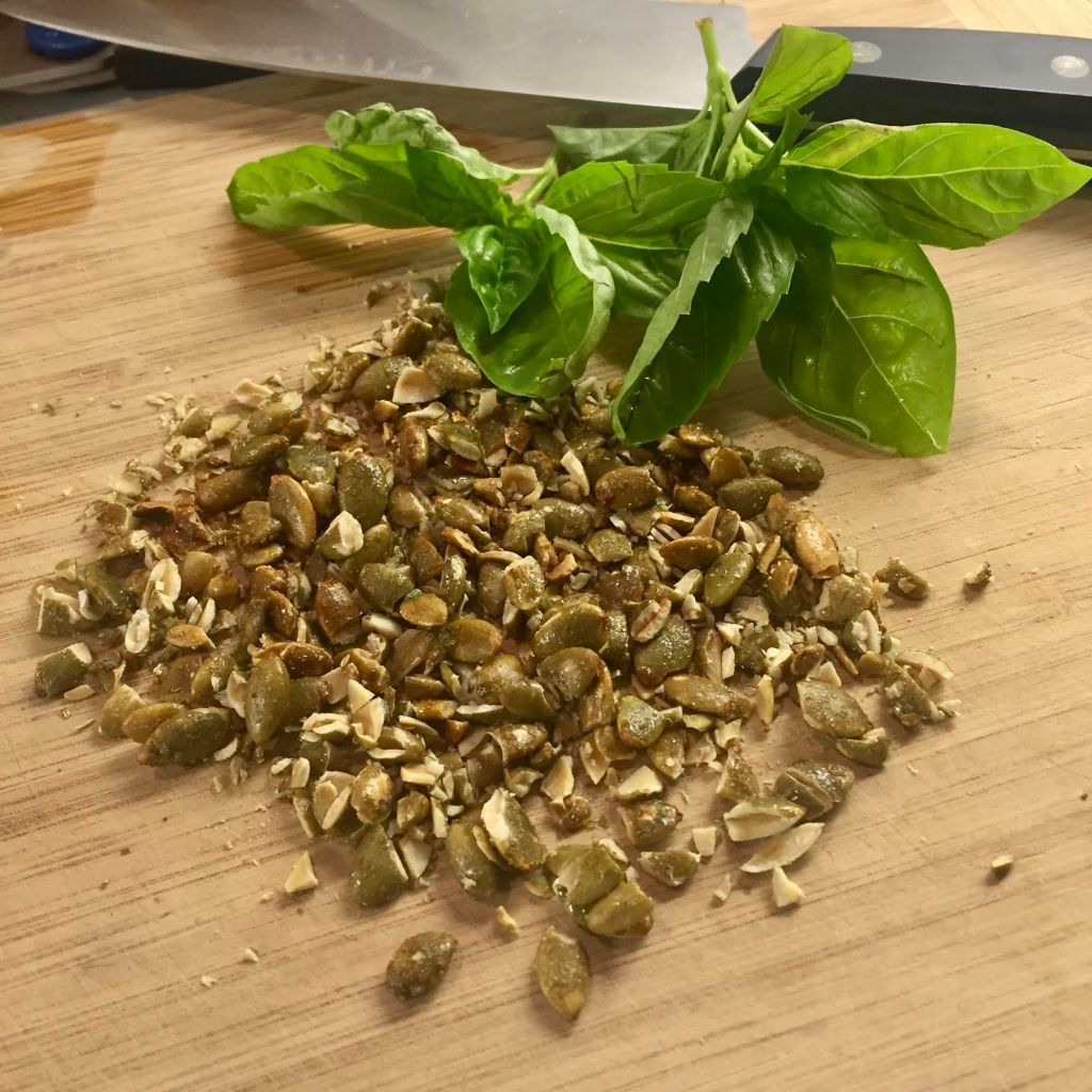 Chopped Maple Sugar & Sea Salt Superseedz with fresh basil leaves on a wooden cutting board.