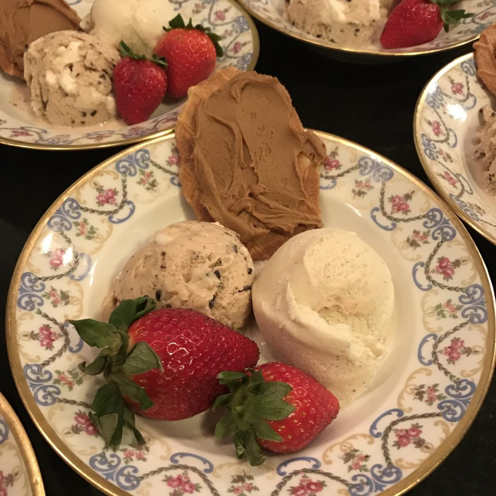 Cookie spread on a butter cookie with two scoops of ice cream and two strawberries in a Limoges bowl.