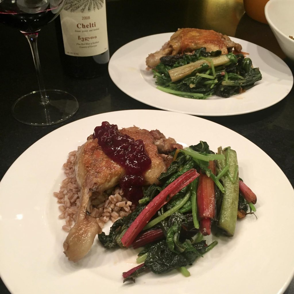 Sauteed duck leg on a white dinner plate with lingdonberries jam and sauteed Swiss chard.