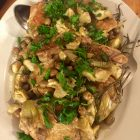 Braised chicken thighs with artichokes, garnished with parsley, on a platter.