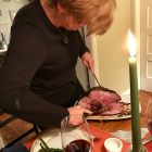 Woman carving a medium rare half-leg of lamb.