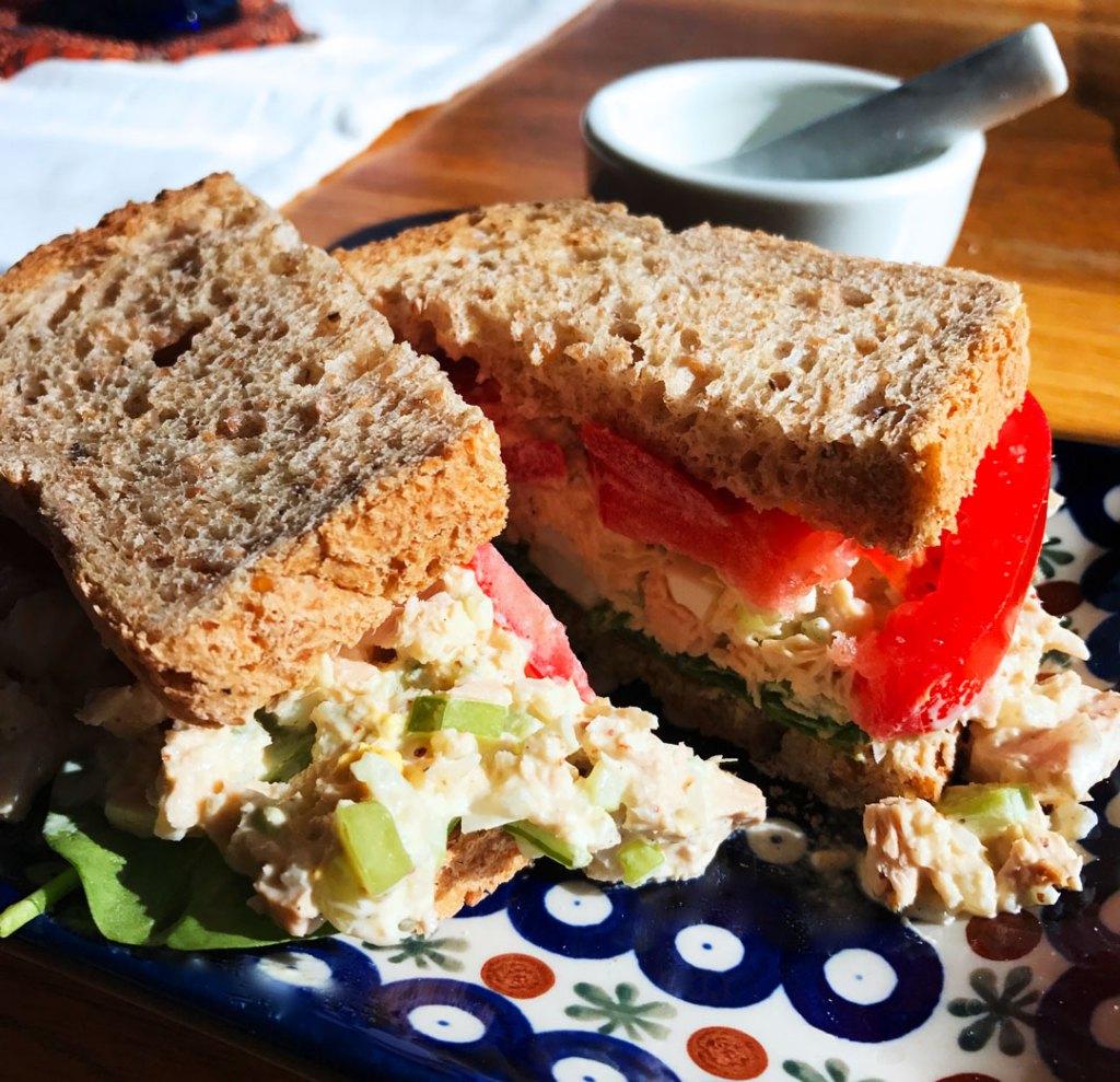 Holy Schmitt's Horseradish tuna salad sandwich cut in half on a blue and white plate.