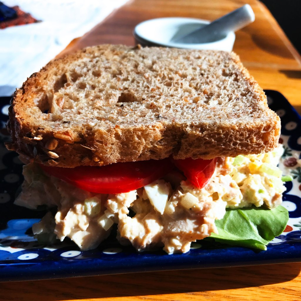 Whole Tuna Salad Sandwiches with Holy Schmitt's Mustard Horseradish on a blue and white plate.