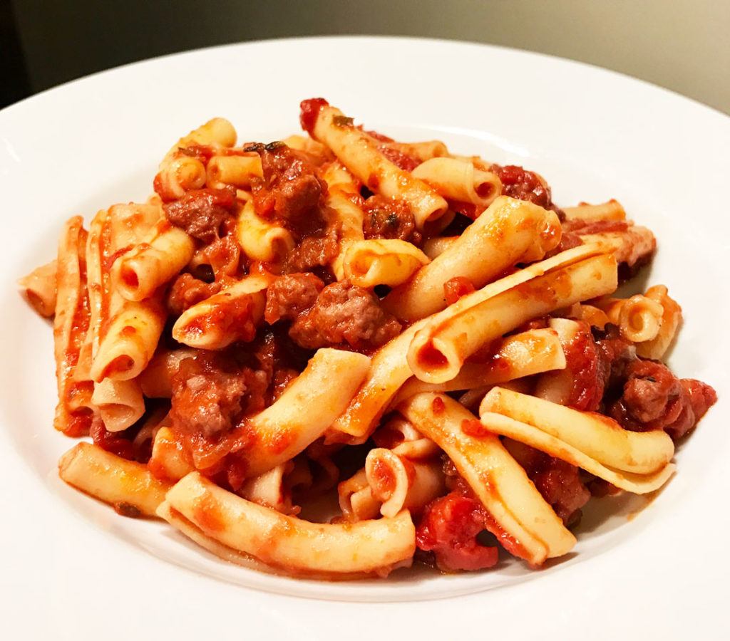 Quick pasta with sweet sausage bolognese in a white bowl - close-up photo.