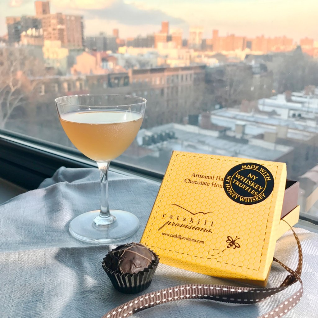 Catskill Provisions NY Honey Whiskey Truffles with cocktail and window in the background.
