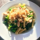 Pasta with Pancetta, Chicken, Pecorino and Broccoli Rabe in a white bowl in the sunlight.