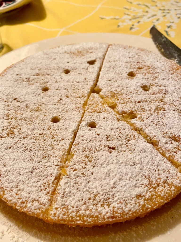Lemon Ricotta cake with powdered sugar and birthday candle holes.