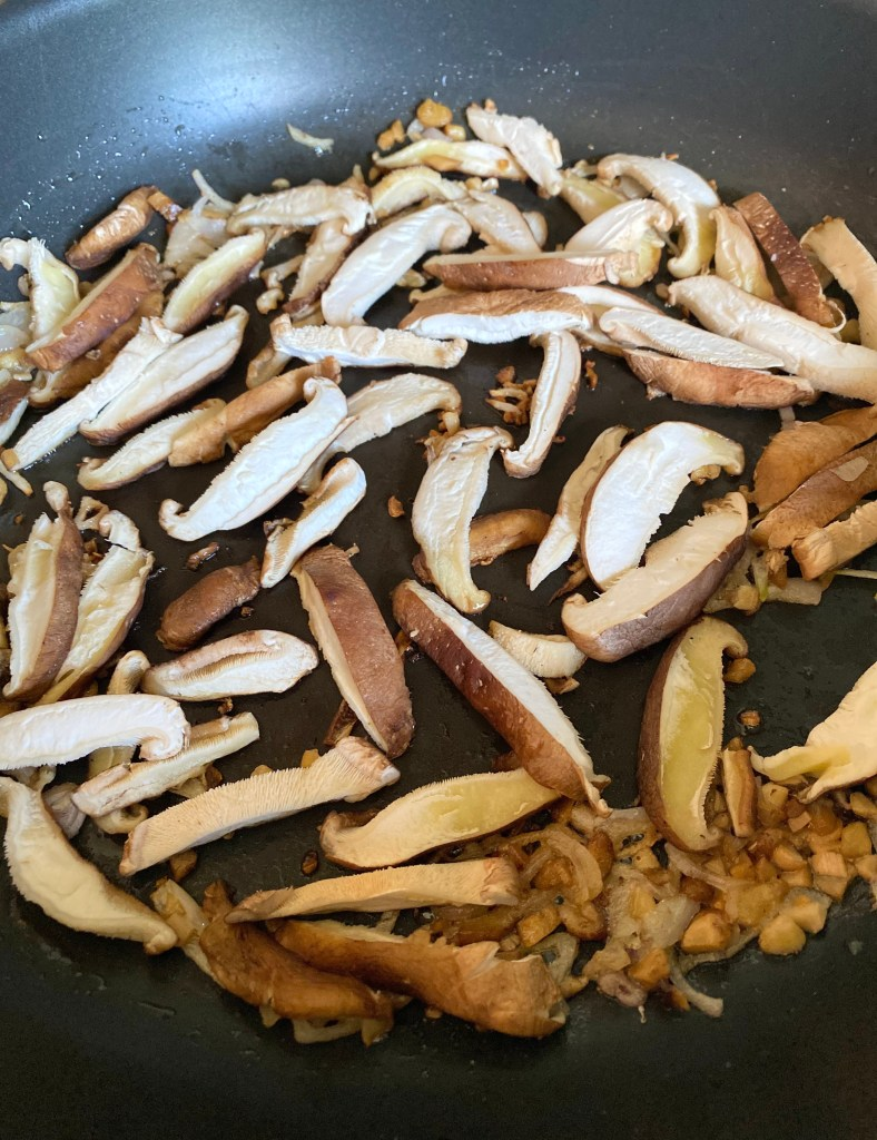 Shiitake mushrooms caps, minced stems and shallots sauteing in a skillet.