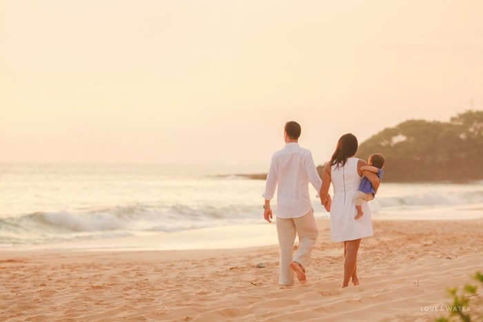 Family walking on beach at sunset on Maui