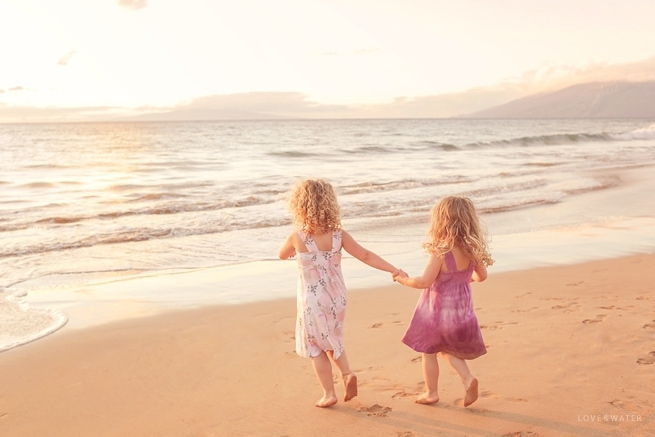 Sisters running on the beach in Maui