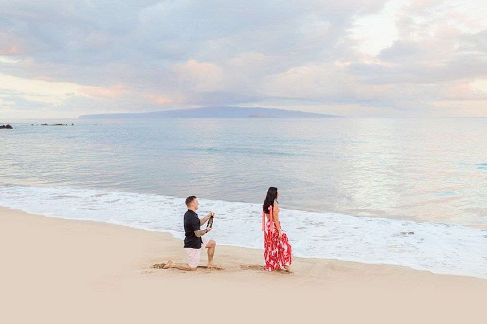 A man holding a bottle of champagne down on one knee while his girlfriend looks out at the ocean, about to propose on the beach in Wailea, Maui.