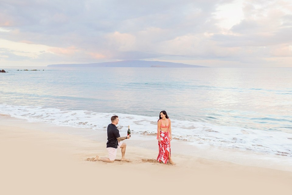 A happily surprised woman turns to see her boyfriend down on one knee with a bottle of champagne during a beach proposal in Hawaii.