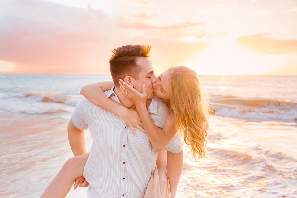 A woman kisses her new fiance while he piggy-backs her on the beach for engagement photos with Love + Water in Maui.