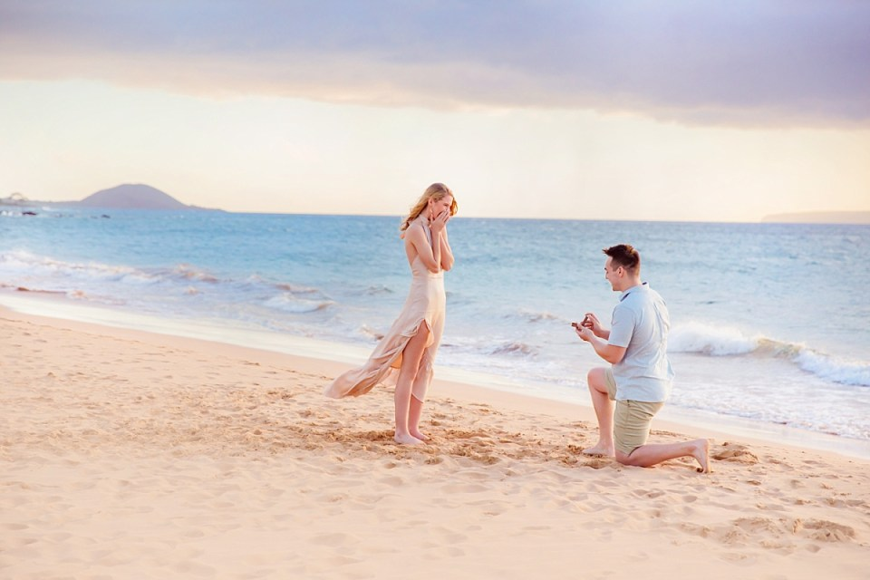 A beautiful woman is surprised while a man presents a ring down on one knee during a beach proposal in Maui, and the moment is captured by Wailea engagement photographers Love + Water photography.