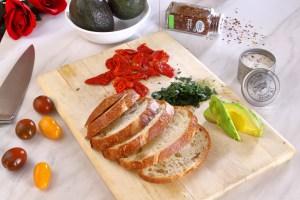 Sliced artisan bread, sliced avocados, sun dried tomatoes and italian parsley