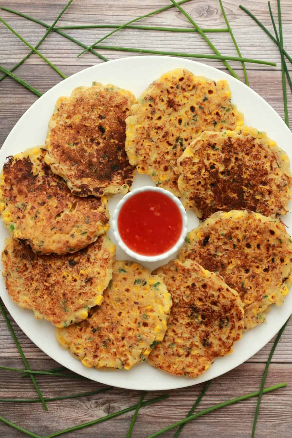 Vegan corn fritters on a white plate with a bowl of sweet chili sauce.