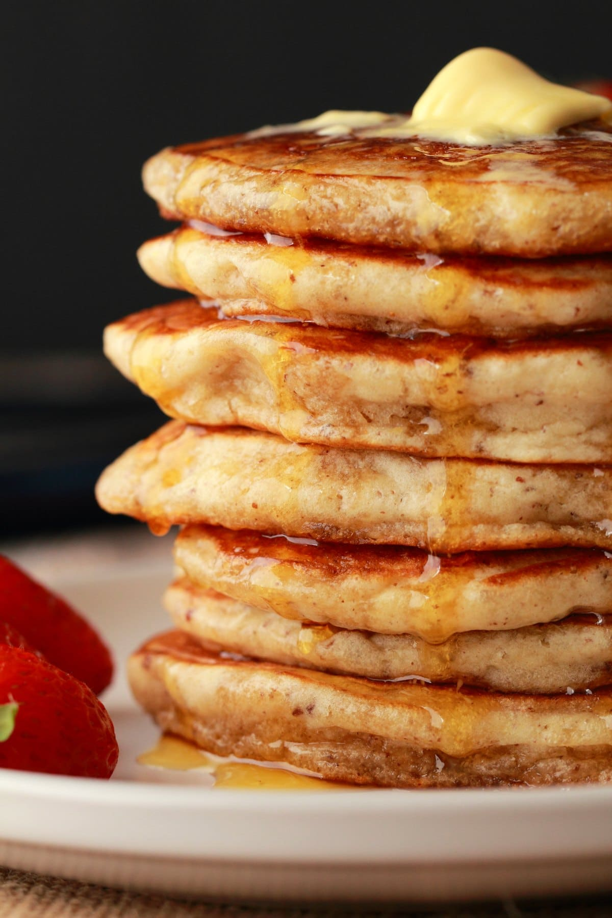A stack of vegan pancakes with melted butter on top and syrup drizzling down the sides.