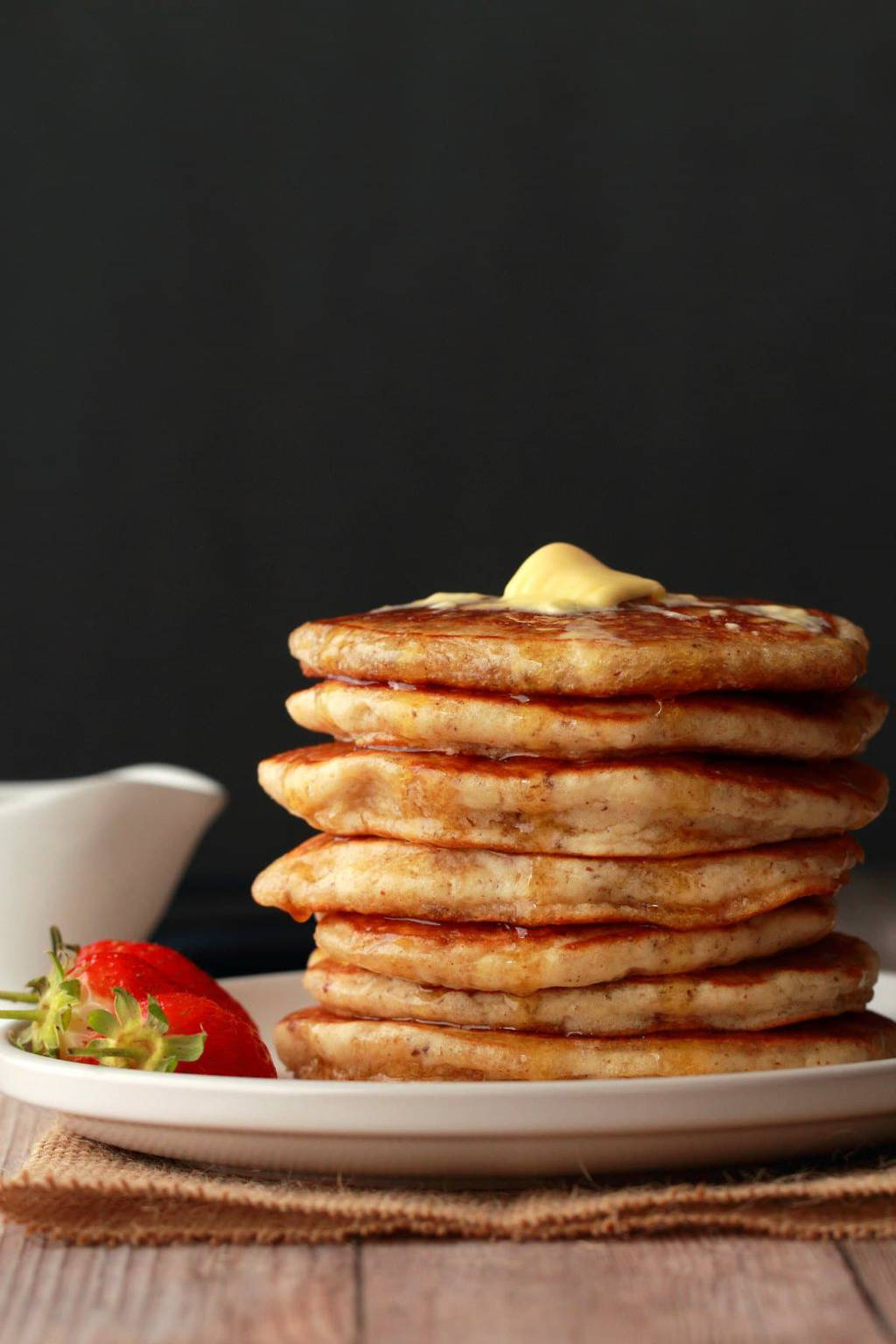 A stack of vegan pancakes with a pat of melting butter on top and drizzles of syrup running down the sides.