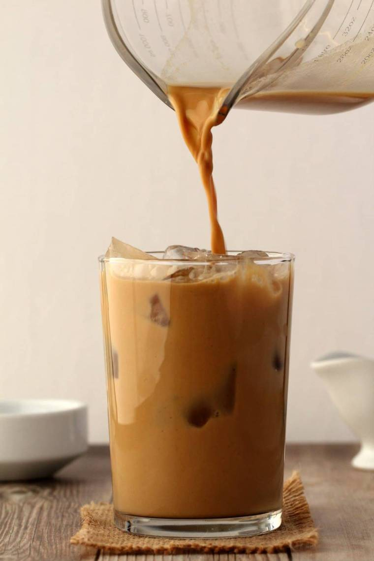 Vegan Iced Coffee pouring from a jug into a glass full of ice.
