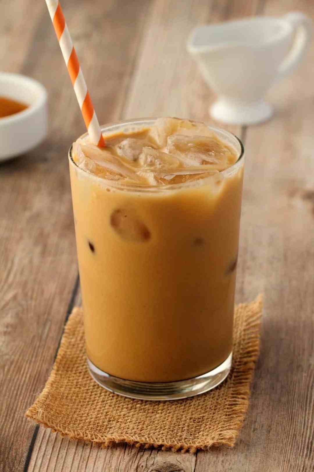 Vegan Iced Coffee in a glass with an orange and white straw.