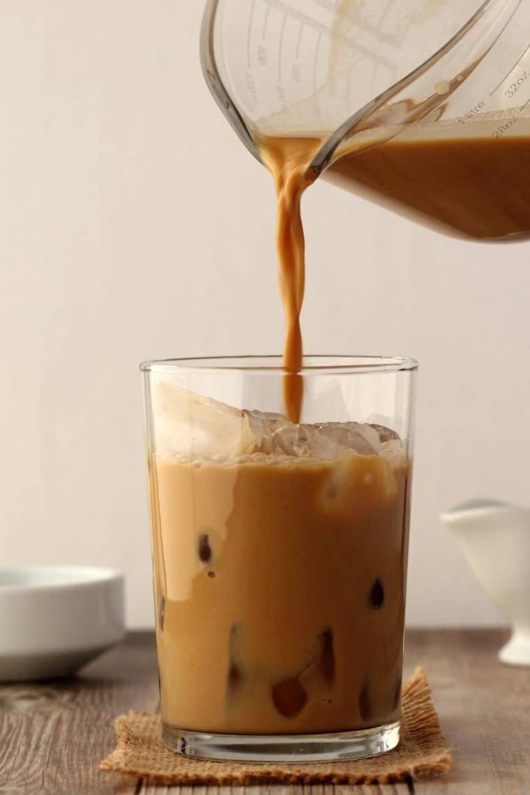 Vegan Iced Coffee pouring into a glass full of ice.