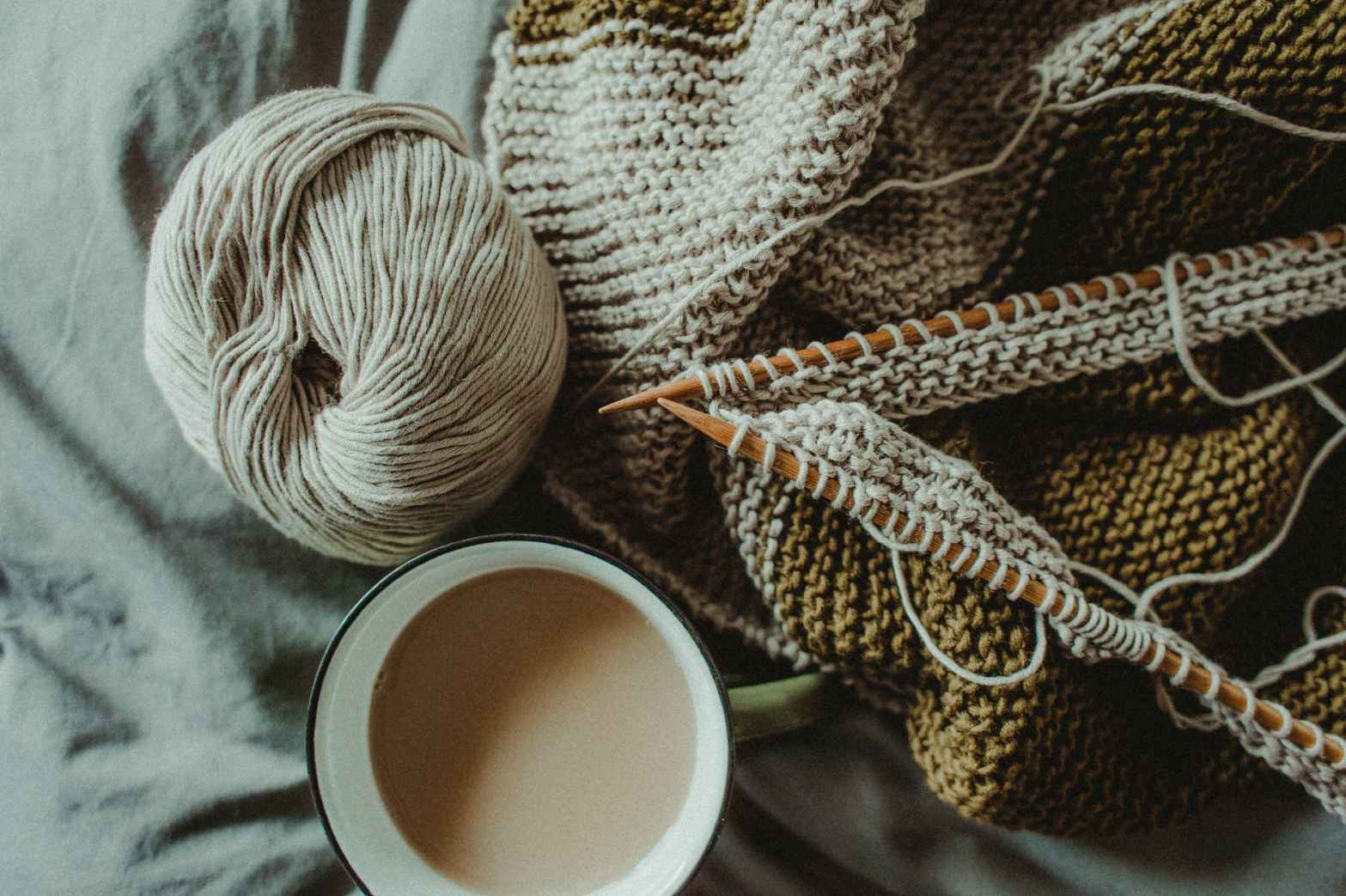 knitting supplies and cup of coffee placed on bed