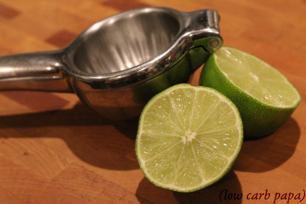 Lime and stainless steel juicer on a wood cutting board