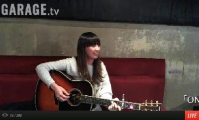 Natsuko Miyamoto clutching a guitar on a live webstream