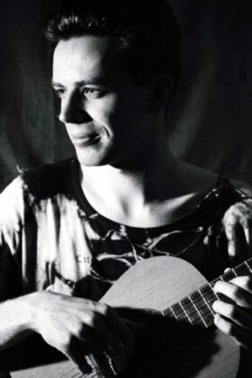Portrait photograph of Jim holding a classical guitar with just the top of it showing in a head and shoulders shot