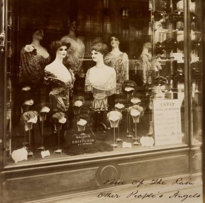 Front cover to the re-issue of the Voice Of The Rain Album Other Peoples Angels which is a photograph, Boulevard de Strasbourg, taken in 1912 of a window display of hair pieces including several female mannequins