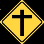 Road side information style sign in black on yellow showing a cross
