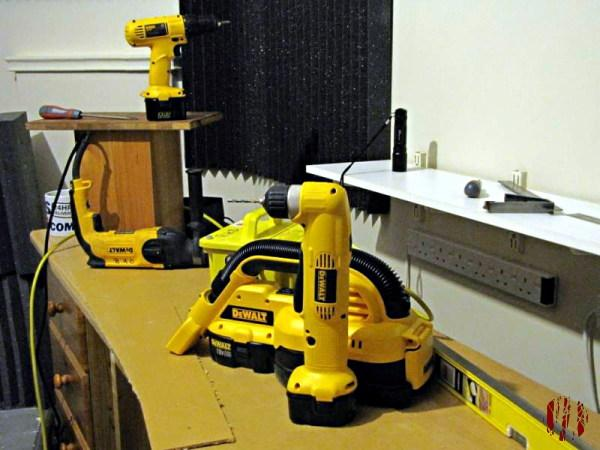 Photograph of ongoing work involving four different tools from DeWalt in their distinctive bright yellow. It's a small site hoover, a right-angled drill and mains and battery powered standard drills.