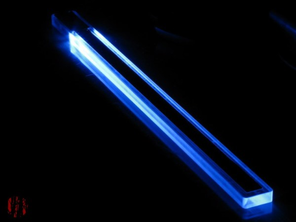 Long thin Eowave ribbon controller made largely from a perspex block lit up by a blue LED at one end against a pitch black background.