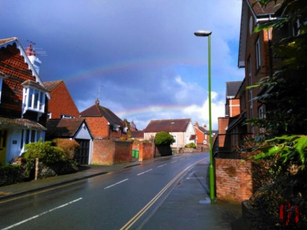 Double rainbow above road and houses with a stormy sky clearing to blue.