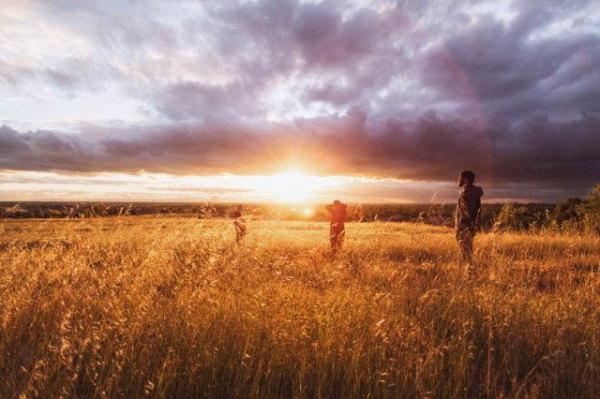 Three ne're do wells spoil a setting sun across grass lands