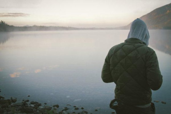 Someone in the way of the view of a misty lake with their back to the camera with hands raised as if rolling a joint