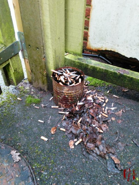 A rusted metal tin used as an outside ashtray by the bins of Mill River Lodge Horsham overflowing with rainwater and causing the cigarettes once in it out onto the surrounding floor.