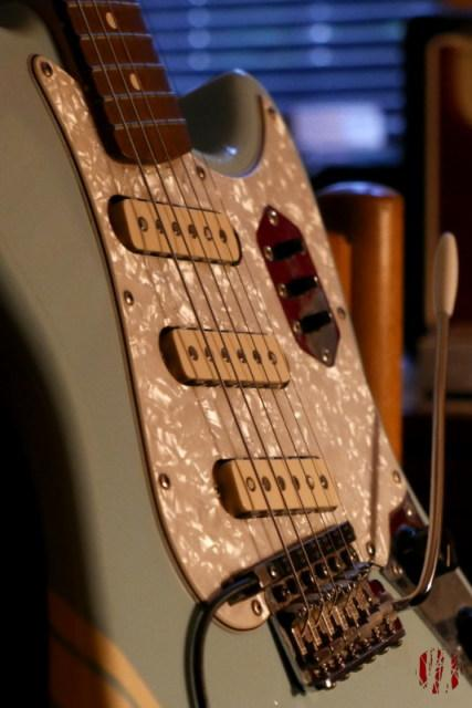 Close up of the pickguard area of a light blue Fender Cyclone 2 guitar seen in the warm glow of led lighting