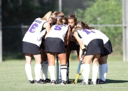 Girls hockey team in huddle on pitch