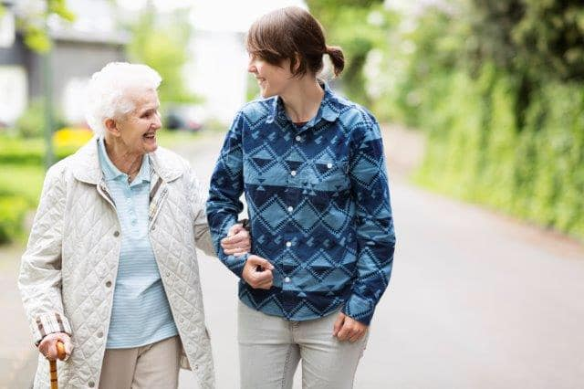 Younger woman walking arm in arm with elderly lady
