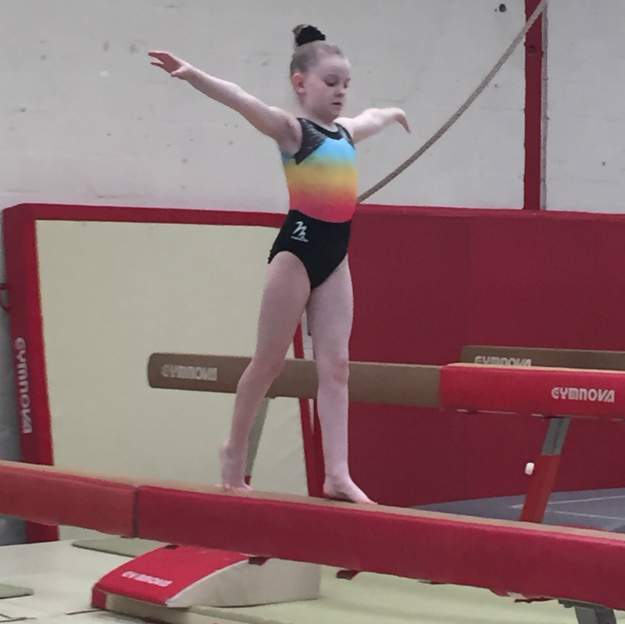Young girl gymnasts balances on a bar at Tumbles Academy of Gymnastics in Lowton